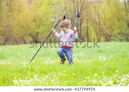 A little boy walks through the grass near the campsite with the sticks.