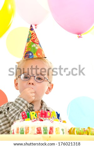 A little boy wearing a party hat sitting in front of a birthday cake.