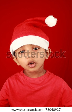 A little boy wearing a santa hat in a red background