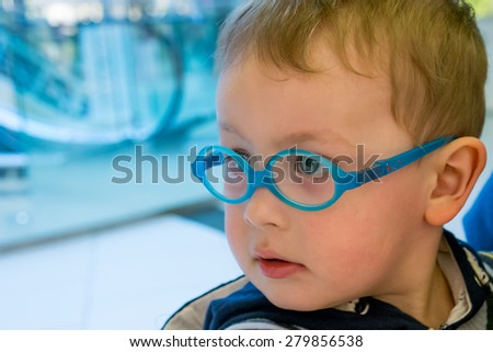 A little boy wearing glasses looks with a serious face - stock photo