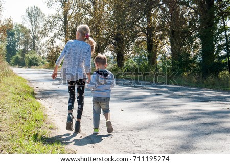 A little boy with a girl is walking along the road.