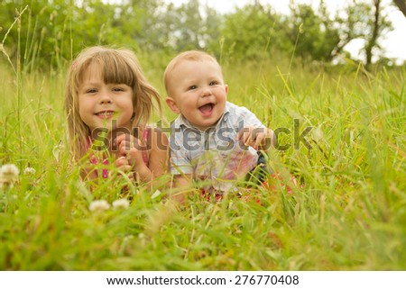 a little brother and sister playing in the nature - stock photo