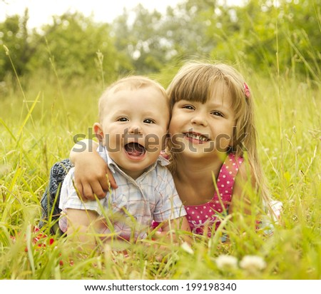 a little brother and sister playing on the nature  - stock photo