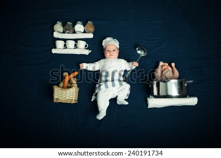 A little chef. A little baby in cook suit with chicken and vegetables on blue background. - stock photo