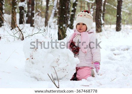 A little child girl sculpts snowman in winter landscape, winter concept, family spending time outdoors - stock photo