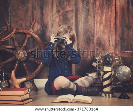 A little child is holding an old retro camera with travel objects in the background for a vacation art concept. - stock photo