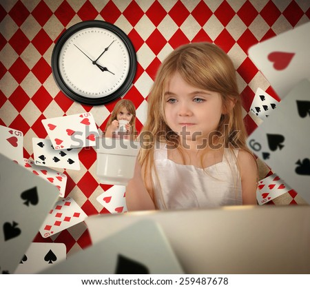 A little child is holding up a tea cup with herself inside with playing cards floating around her for a fairytale or imagination concept. - stock photo
