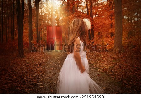 A little child is in the woods wearing a white dress and looking at a glowing red door behind her on a wood path for a mystery or imagination concept. - stock photo