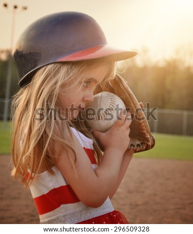 A little child is playing a game of baseball on the dirt field with a glove mitt on for a sport or recreation concept. - stock photo