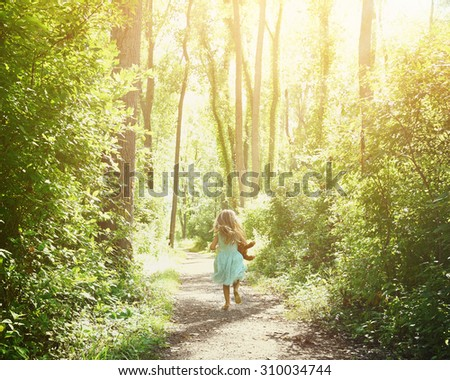 A little child is running down a nature trail with sunlight on the trees for a happiness or freedom concept. - stock photo