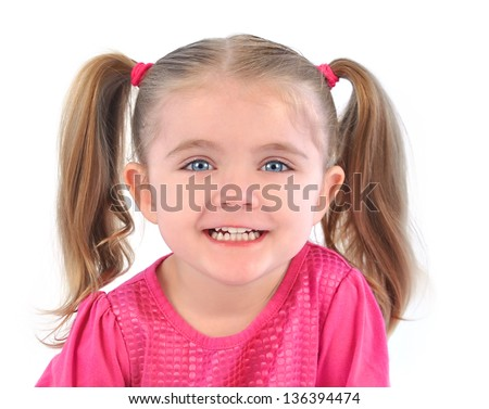 A little child is wearing a pink shirt with pig tails in her hair and is laughing with happiness. The girl is on a white isolated background. - stock photo
