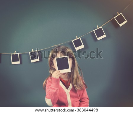 A little child photographer is holding up a photo of a blank film print and other photos on the wall for a art or creativity concept. - stock photo