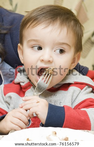 A little child using the fork to eat for his first time.