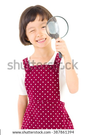 A little chinese girl peers at the camera through a magnifying glass, isolated on white background - stock photo