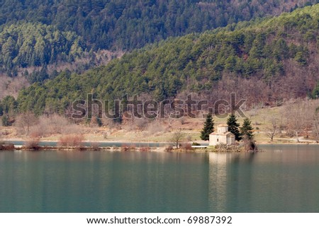 A little church on the edge of a narrow band of land, in Doksa lake, Greece