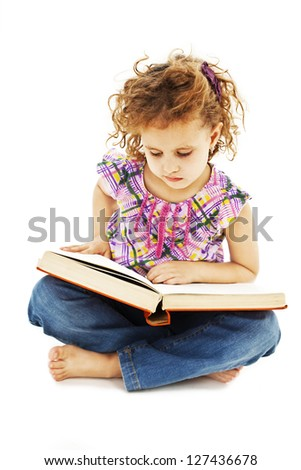 A little curly girl reading a book on the floor. Isolated on white background