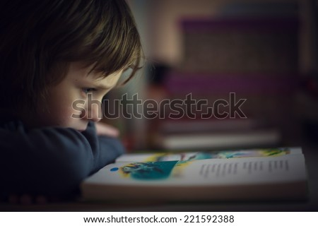 A little cute boy reading a book close up - stock photo