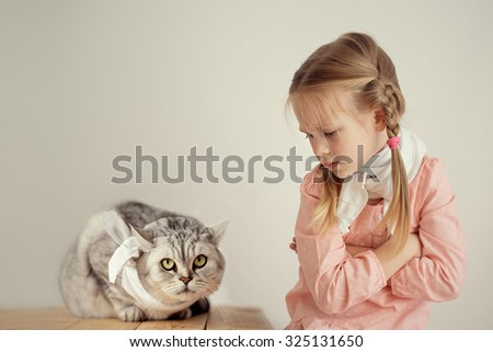 A little cute girl and a cat both with a sore throat close up. Children and pets. - stock photo