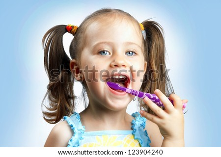 A little cute girl brushing her teeth - stock photo
