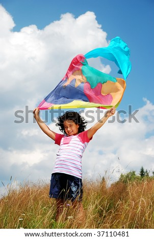 A little cute girl holding scarf on wind, outdoor