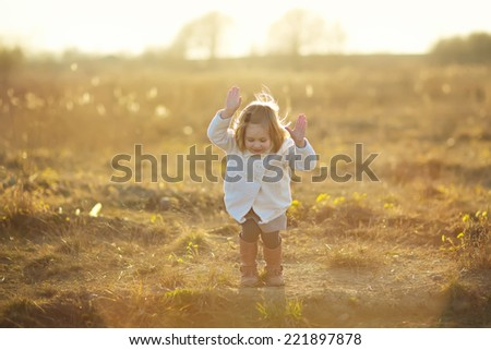 A little cute girl jumping in the field in summer morning.  - stock photo