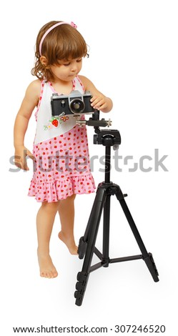 A little cute girl making making a shot with camera on tripod isolated on white background - stock photo