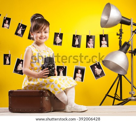 A little cute girl making photo on yellow background.  - stock photo
