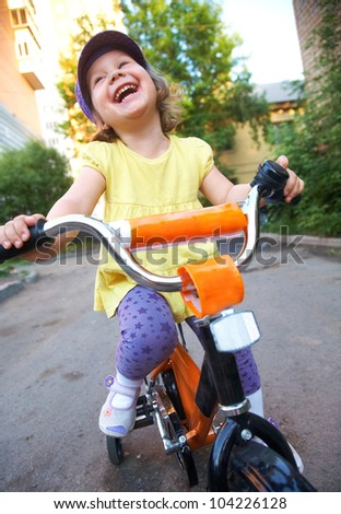 A little cute girl rides a bicycle down the street - stock photo