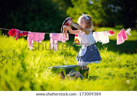 A little cute girl washing her doll and doing the laundry in a small aluminium basin near the clothesline in the meadow on a sunny summer day - stock photo