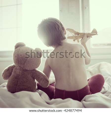 A little cute kid with Teddy bear in bedroom - stock photo