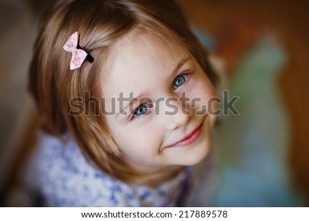A little cute smiling girl looking upwards close up. - stock photo