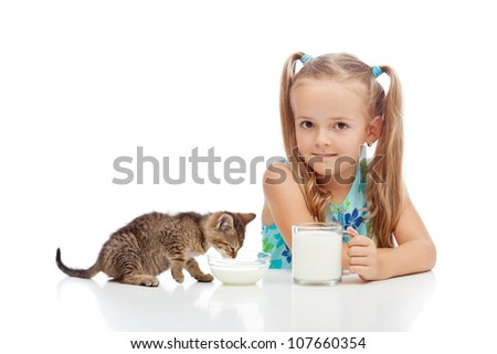 A little fresh milk for the little ones - girl and her kitten drinking, isolated - stock photo