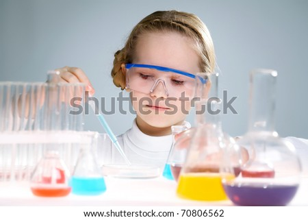 A little girl analyzing chemical liquid