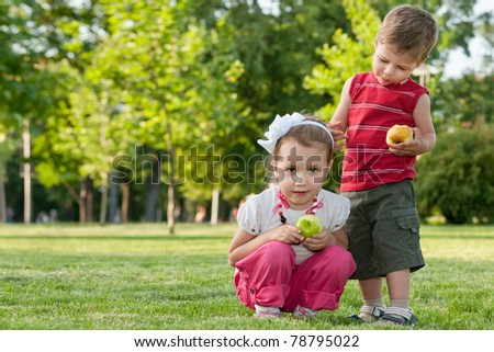 A little girl and a boy are holding apples