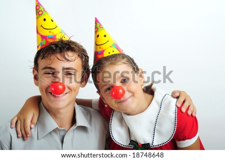 A little girl and a boy with party horn and clown noses - stock photo