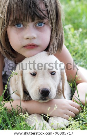 A little girl and her puppy, an English Cream Labrador-Golden Retriever mixed designer breed 7 week old puppy,  resting after playing together. Extreme shallow dof.