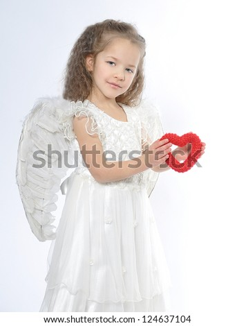 A little girl angel stands with a heart in her hands symbolizing the heart of children - Charity, love, compassion - stock photo
