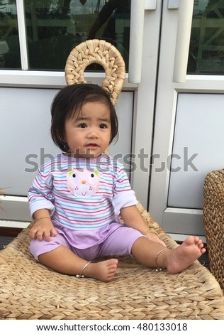A little girl Asia sitting on chair