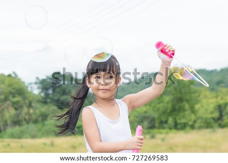 A little girl blowing soap bubbles in summer park.