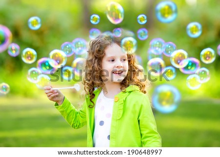 A little girl blowing soap bubbles, spring portrait beautiful curly hair.