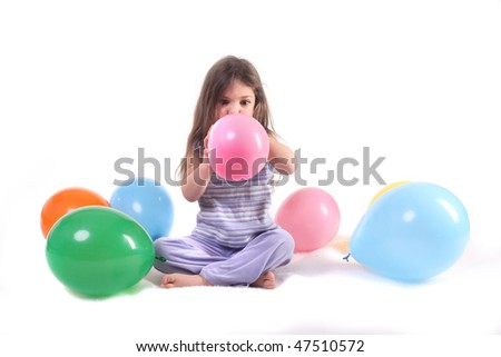 a little girl blowing up a balloon surrounded by balloons - stock photo