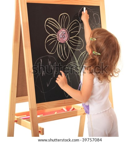 A little girl draws a chalk on a board.