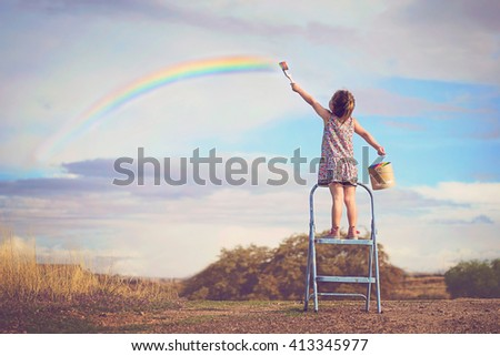 A little girl draws a rainbow standing on a ladder and holding a paint can