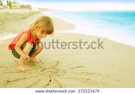 a little girl draws a sun in the sand on the beach - stock photo
