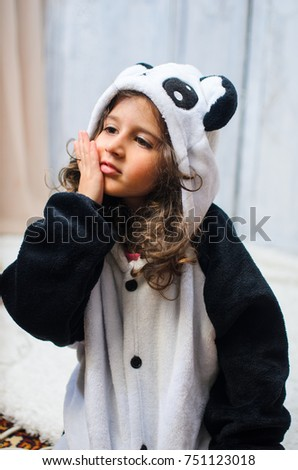 a little girl dressed in a bear costume Panda.