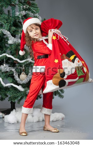 A little girl dressed in a suit Santa Claus standing near a Christmas tree and holding a red bag with gifts