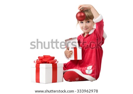 a little girl dressed in Christmas clothes. she sits on the floor and opens a box with a gift