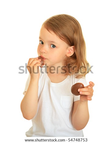 A little girl eating a delicious chocolate.