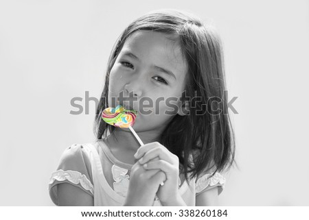 a little girl eating a lollipop - stock photo