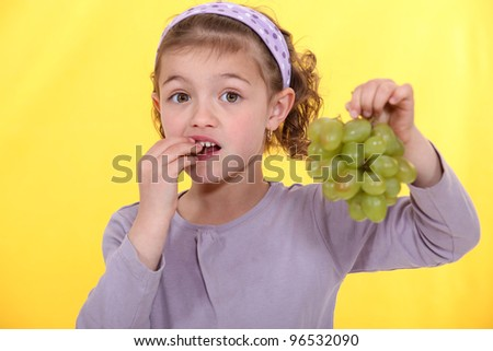 A little girl eating grapes.